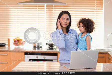 Mother and daughter with cellphone and laptop in the kitchen tog stock photo, Young mother and daughter with cellphone and laptop in the kitchen together by Wavebreak Media