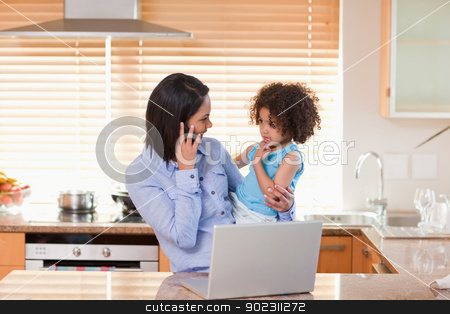 Mother and daughter with cellphone and notebook in the kitchen t stock photo, Young mother and daughter with cellphone and notebook in the kitchen together by Wavebreak Media