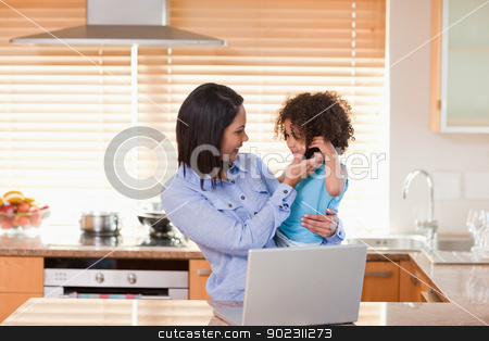 Mother and daughter using laptop and cellphone in the kitchen to stock photo, Young mother and daughter using laptop and cellphone in the kitchen together by Wavebreak Media