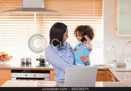 Mother and daughter using notebook and cellphone in the kitchen  stock photo, Young mother and daughter using notebook and cellphone in the kitchen together by Wavebreak Media