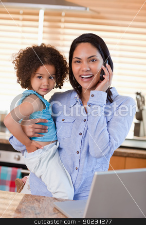 Mother and daughter using cellphone in the kitchen together stock photo, Young mother and daughter using cellphone in the kitchen together by Wavebreak Media