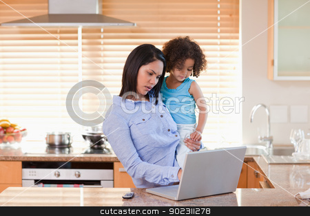 Mother and daughter using laptop in the kitchen together stock photo, Young mother and daughter using laptop in the kitchen together by Wavebreak Media