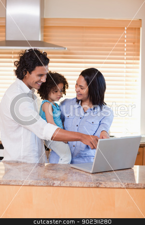 Family using notebook in the kitchen together stock photo, Young family using notebook in the kitchen together by Wavebreak Media