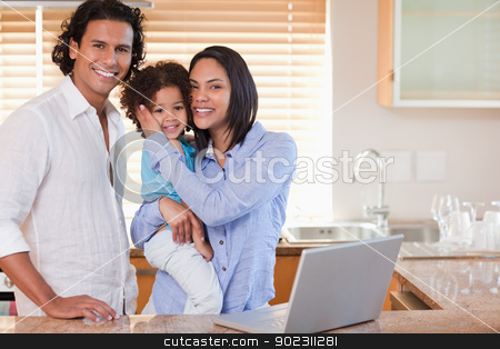 Family surfing the internet in the kitchen together stock photo, Young family surfing the internet in the kitchen together by Wavebreak Media