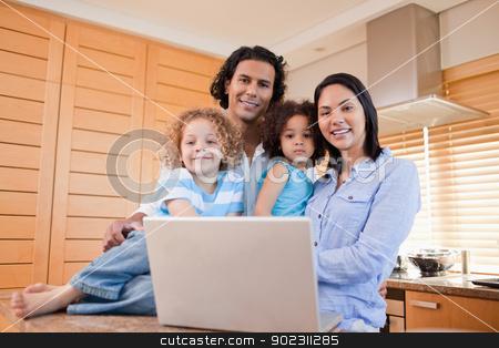 Happy family with laptop standing in the kitchen together stock photo, Happy young family with laptop standing in the kitchen together by Wavebreak Media