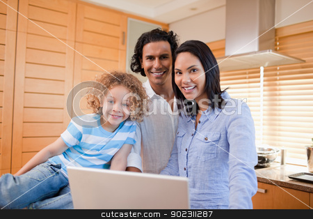 Cheerful family surfing the internet in the kitchen together stock photo, Cheerful young family surfing the internet in the kitchen together by Wavebreak Media