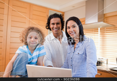 Joyful family surfing the internet in the kitchen together stock photo, Joyful young family surfing the internet in the kitchen together by Wavebreak Media