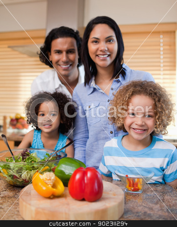 Family with salad together in the kitchen stock photo, Young family with salad together in the kitchen by Wavebreak Media