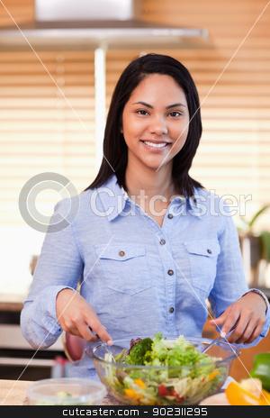 Smiling woman in the kitchen stirring salad stock photo, Smiling young woman in the kitchen stirring salad by Wavebreak Media