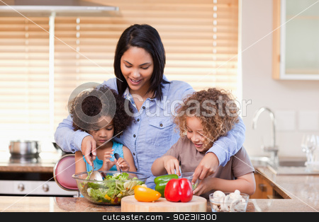 Mother and daughters preparing salad in the kitchen together stock photo, Young mother and daughters preparing salad in the kitchen together by Wavebreak Media