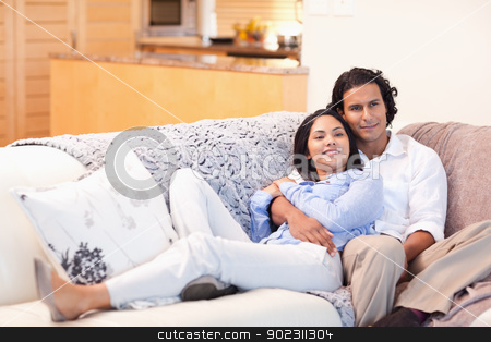 Happy couple on the couch together stock photo, Happy young couple on the couch together by Wavebreak Media