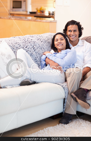 Happy couple relaxing on the couch together stock photo, Happy young couple relaxing on the couch together by Wavebreak Media