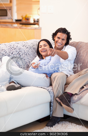 Cheerful couple watching television together stock photo, Cheerful young couple watching television together by Wavebreak Media