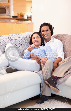 Happy couple watching television together stock photo, Happy young couple watching television together by Wavebreak Media