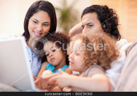 Happy family using laptop together stock photo, Happy young family using laptop together by Wavebreak Media