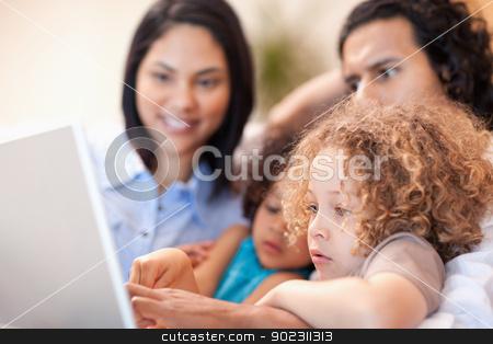 Cheerful family using laptop together stock photo, Cheerful young family using laptop together by Wavebreak Media