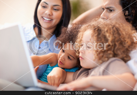 Family having a good time at the laptop together stock photo, Young family having a good time at the laptop together by Wavebreak Media