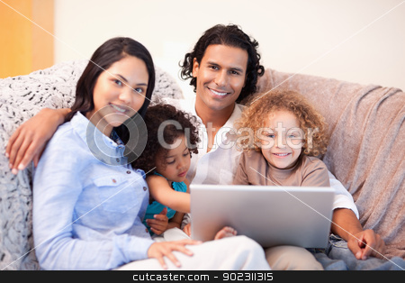 Family using laptop on the sofa together stock photo, Young family using laptop on the sofa together by Wavebreak Media