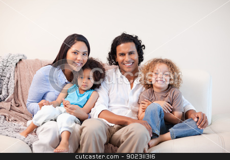 Cheerful family sitting on the sofa together stock photo, Cheerful young family sitting on the sofa together by Wavebreak Media