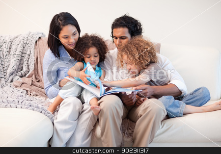 Family on the sofa looking at photo album together stock photo, Young family on the sofa looking at the photo album together by Wavebreak Media