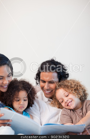 Cheerful family on the sofa looking at photo album together stock photo, Cheerful young family on the sofa looking at photo album together by Wavebreak Media