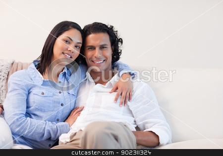 Couple on the sofa hugging stock photo, Young couple on the sofa hugging by Wavebreak Media