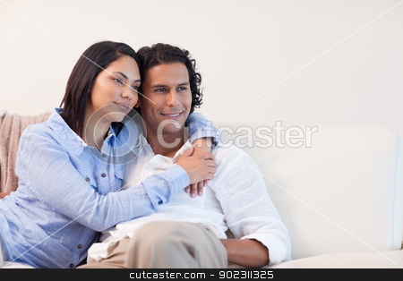 Couple on the couch hugging stock photo, Young couple on the couch hugging by Wavebreak Media