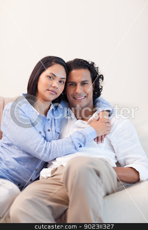 Couple on the couch embracing stock photo, Young couple on the couch embracing by Wavebreak Media