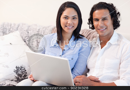 Couple with laptop on the sofa stock photo, Young couple with laptop on the sofa by Wavebreak Media