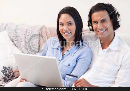 Couple with notebook on the sofa stock photo, Young couple with notebook on the sofa by Wavebreak Media