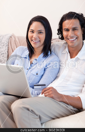 Couple with notebook on the couch stock photo, Young couple with notebook on the couch by Wavebreak Media