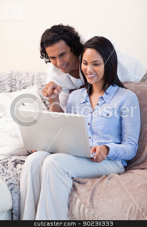 Couple on the sofa surfing the internet together stock photo, Young couple on the sofa surfing the internet together by Wavebreak Media