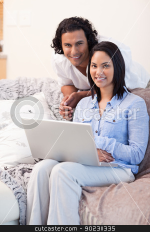 Couple surfing the internet on the couch stock photo, Young couple surfing the internet on the couch by Wavebreak Media