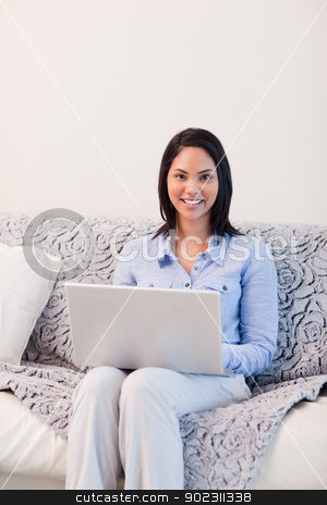 Smiling woman on the sofa surfing the internet stock photo, Smiling young woman on the sofa surfing the internet by Wavebreak Media