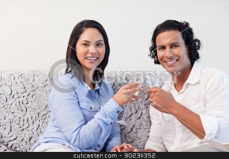Couple having sparkling wine on the sofa stock photo, Young couple having sparkling wine on the sofa by Wavebreak Media