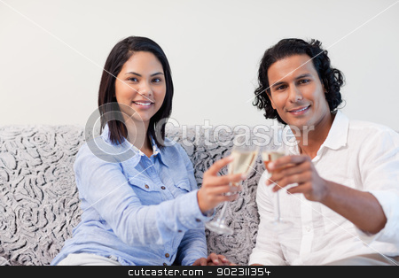 Couple celebrating with sparkling wine on the sofa stock photo, Young couple celebrating with sparkling wine on the sofa by Wavebreak Media