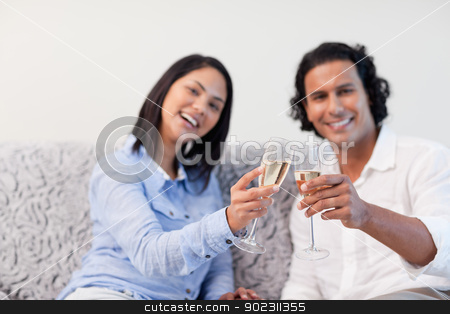 Couple celebrating with sparkling wine on the couch stock photo, Young couple celebrating with sparkling wine on the couch by Wavebreak Media