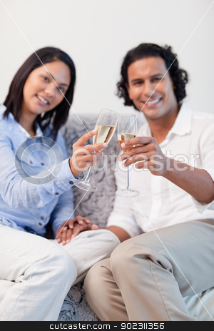 Couple celebrating with sparkling wine in the living room stock photo, Young couple celebrating with sparkling wine in the living room by Wavebreak Media