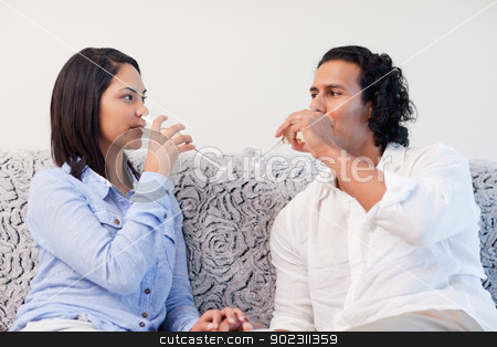 Couple drinking sparkling wine in the living room stock photo, Young couple drinking sparkling wine in the living room by Wavebreak Media