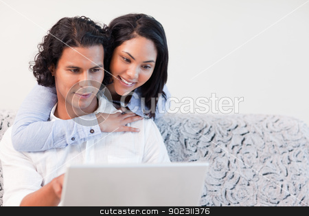 Couple on the laptop together stock photo, Young couple on the laptop together by Wavebreak Media