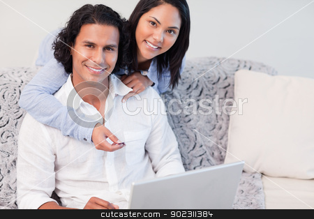 Couple shopping online together stock photo, Young couple shopping online together by Wavebreak Media