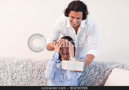 Man having a present for his girlfriend stock photo, Young man having a present for his girlfriend by Wavebreak Media