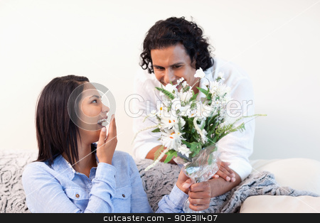Man giving his girlfriend a bouquet stock photo, Young man giving his girlfriend a bouquet by Wavebreak Media