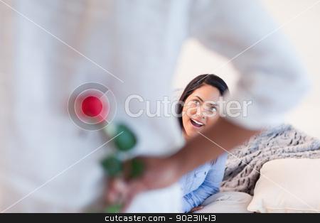 Woman about to get a rose from her boyfriend stock photo, Young woman about to get a rose from her boyfriend by Wavebreak Media
