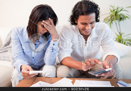 Couple checking their bills in the living room stock photo, Young couple checking their bills in the living room by Wavebreak Media