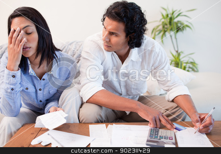Couple checking their bills stock photo, Young couple checking their bills by Wavebreak Media
