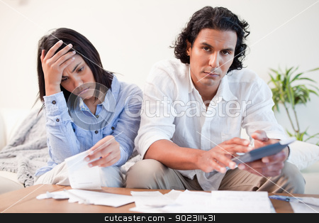 Frustrated couple checking their bills in the living room stock photo, Frustrated young couple checking their bills in the living room by Wavebreak Media