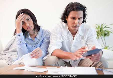 Frustrated couple doing their calculations in the living room stock photo, Frustrated young couple doing their calculations in the living room by Wavebreak Media