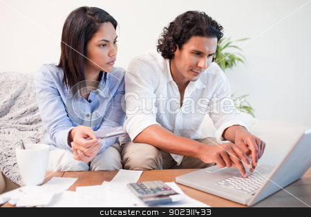 Couple checking their bank accounts online stock photo, Young couple checking their bank accounts online by Wavebreak Media