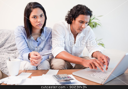 Couple checking their bank accounts online in the living room stock photo, Young couple checking their bank accounts online in the living room by Wavebreak Media